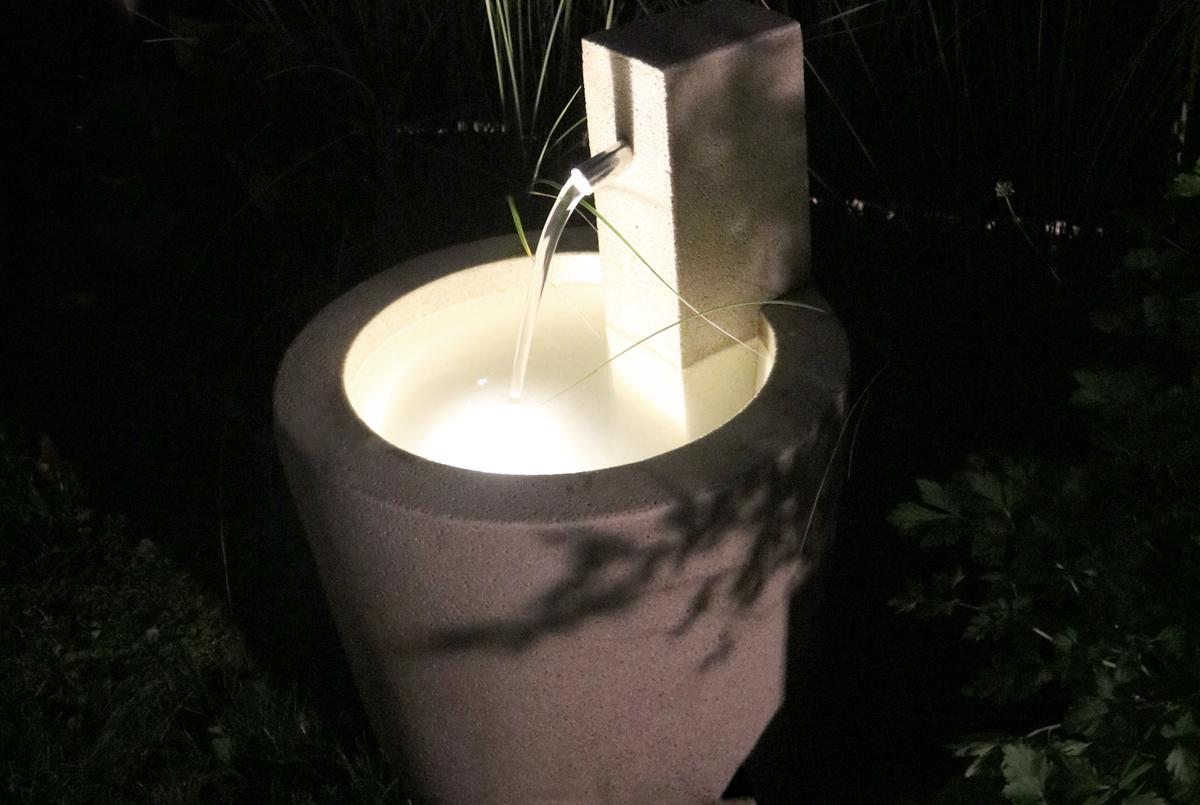Beleuchteter Brunnen im Garten mit LED