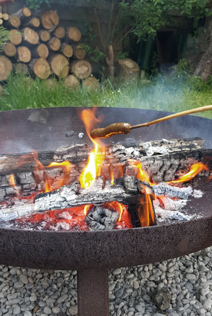 Würstchen am Stock über der Feuerschale